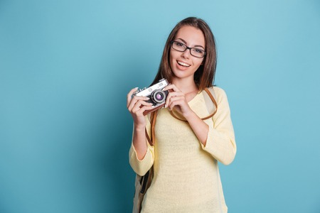 photocamera: Young pretty girl taking photo using photocamera isolated on the blue background