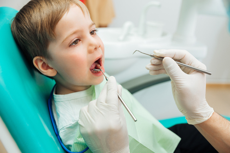mouth opened: Cute little boy sitting with mouth opened during oral checkup at the dentist