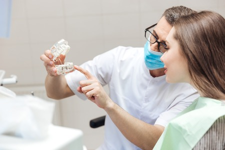 dental surgery: Man dentist show dentures teeth at dental surgery to his patient at the clinic Stock Photo