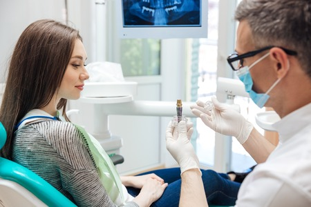 Male dentist showing his female patient a dental implant in clinic Standard-Bild