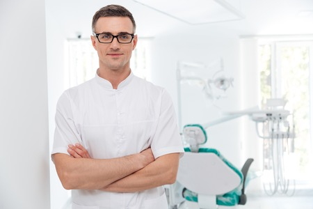 Female dentist standing with his hands crossed and looking at camera photo