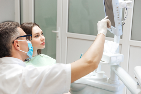 Male dentist is reviewing her x ray on the computer screen in clinic photo