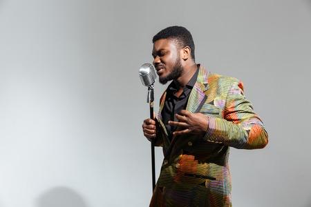 Manierafro het Amerikaanse mens zingen in uitstekende die microfoon op een witte achtergrond wordt geïsoleerd
