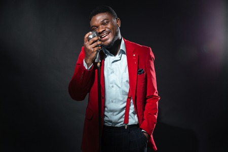 1 man: Stylish afro amerian man singing into vintage microphone over dark background Stock Photo