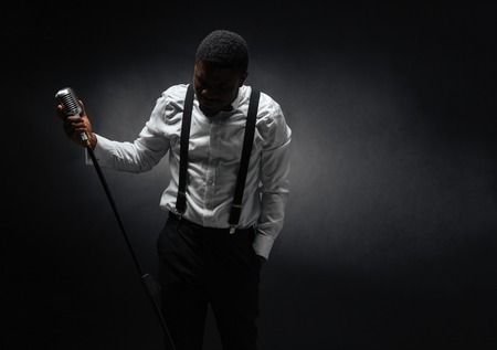 Portrait of afro american male singer posing over dark background