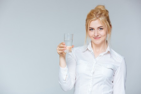 lovely businesswoman: Happy lovely young businesswoman holding glass of water over white background Stock Photo