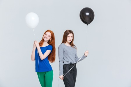 dissimilarity: Two cheerful and upset young women holding black and white balloons