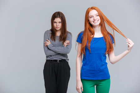 Two smiling redhead and upset brunette young women standing over white background