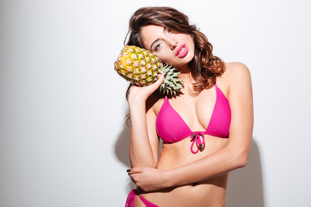 etalon: Pretty young beautiful beach girl in bikini holding pineapple isolated on the white background