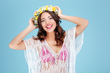 woman pose: Close-up portrait of a beautiful brunette wearing flower wreath isolated on the blue background