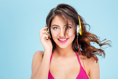 teen bikini: Close-up portrait of smiling attractive girl listening music with earphones isolated on the blue background Stock Photo