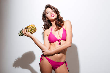 etalon: Beautiful sexy young with perfect body wearing bikini holding a pineapple isolated on the white background