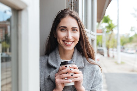 looking away from camera: Happy cheerful smiling girl holding take away coffee and looking at camera at the restaurant Stock Photo
