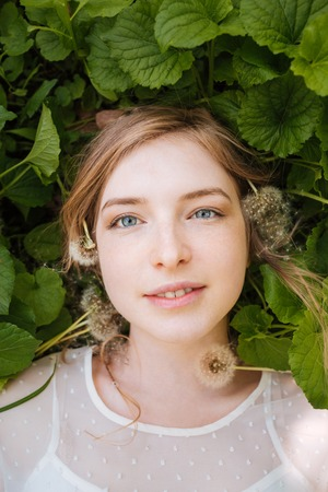 lying on leaves: Top view of cute charming young woman lying on green leaves and dandelions