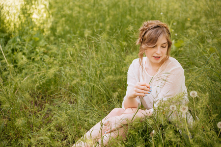 Charming sensual young woman sitting on grass and looking on dandelions