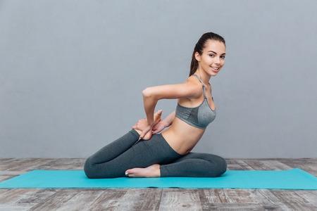 legged: Young woman doing yoga asana Eka Pada Rajakapotasana (one legged king pigeon) isolated on grey background