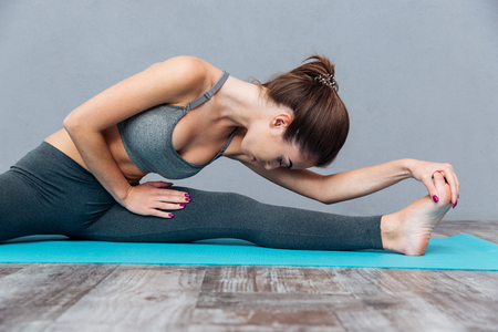 splits: Young healthy fitness woman doing splits isolated on grey background Stock Photo