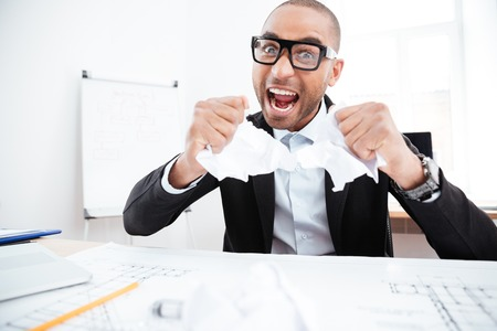 broken contract: Angry businessman tearing up a document, contract or agreement in office Stock Photo