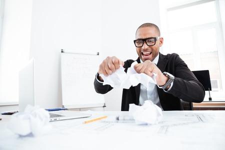 Hombre de negocios enojado que rasga encima de un documento, contrato o acuerdo en el cargo