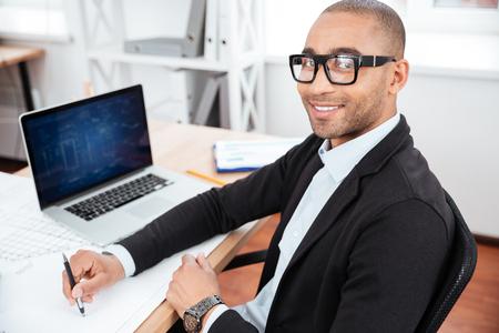 Joven hombre de negocios mirando a la cámara en el escritorio en la oficina Foto de archivo