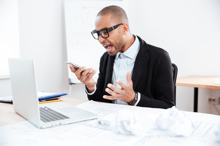 angry boss: Angry businessman in stress working and talking on mobile phone at office desk