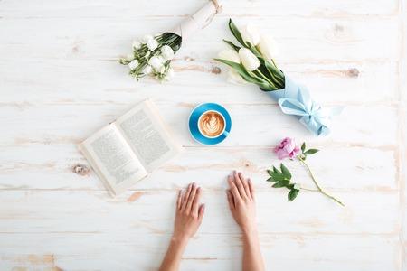 花と木のテーブル広がって女性の手