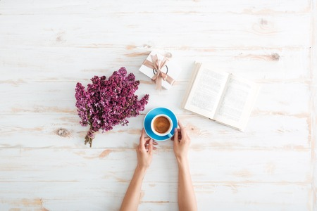 Hands of young woman drinking coffee and reading book on wooden table with flowers and present box Imagens