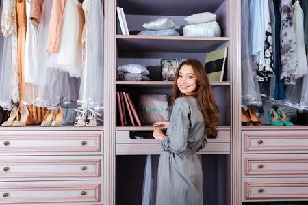 그녀의 옷장에 서있는 아름 다운 젊은 웃는 여자