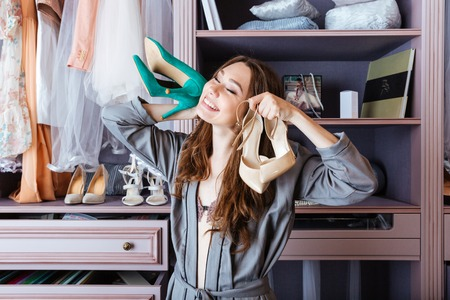 woman searching: Young attractive woman searching for clothing in a closet