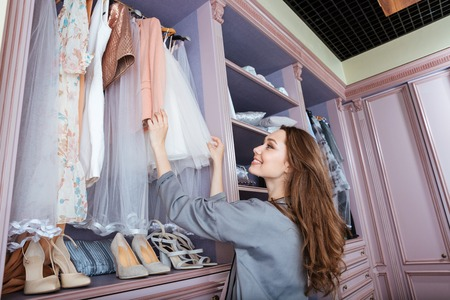 Young attractive smiling woman searching what to wear in a wardrobe Standard-Bild