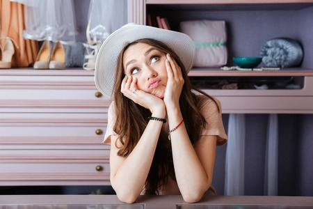 Beautiful young pensive woman thinking about something in her closet Stock Photo