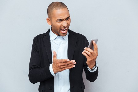 anger management: Close-up portrait of angry young man pointing with finger at his smart phone isolated grey background