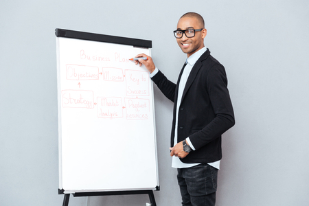 african business man: Smiling african young man in glasses writing business plan on flipchart