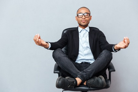 meditating: Closeup of attractive young man in glasses meditating on office chair