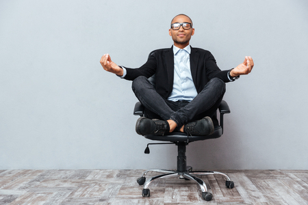 Relaxed handsome african young man sitting and meditating on office chair Фото со стока
