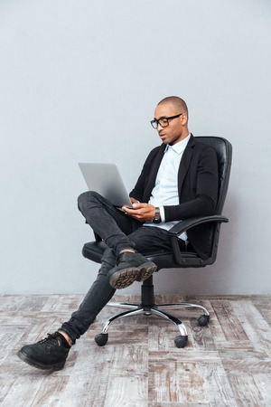 Concentrated young man in glasses sitting in office chair and using laptop