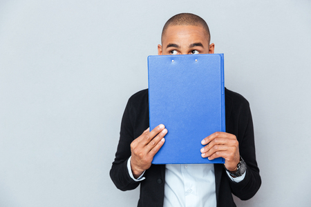 man holding card: Scared shy african american young man covered his face with blue folder