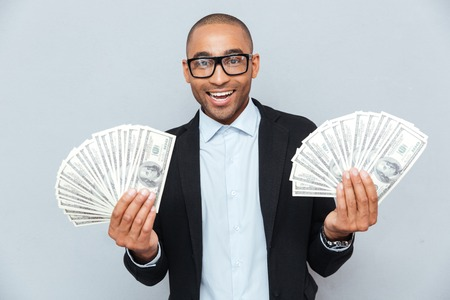 Smiling successful african young man holding a lot of money in both hands Stock Photo