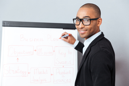 african business man: Handsome african american young man making presentation of business plan on flipchart Stock Photo