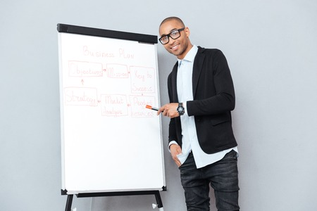 paper board: Cheerful african young businessman using flipchart and pointing on business plan Stock Photo