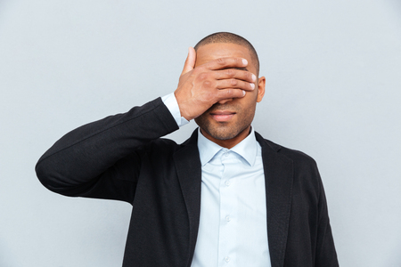 unsighted: Portrait of a businessman covering eyes isolated on gray background