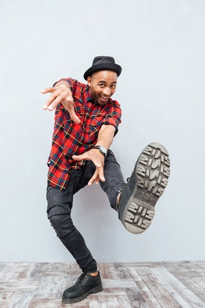 Full length of joyful african man smiling and dancing Stock Photo