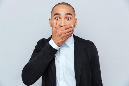 negras africanas: Hombre africano joven hermoso que cubre la boca con la mano aisladas sobre fondo gris