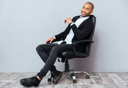 african business man: Happy handsome african american young man sitting in leather office chair