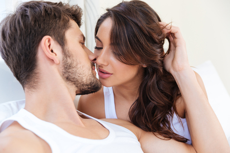 Close-up portrait of a young beautiful pretty kissing couple laying in bed Stock Photo