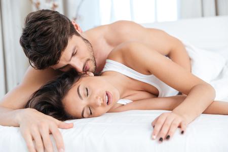 Joven pareja feliz abrazando en la cama en el dormitorio
