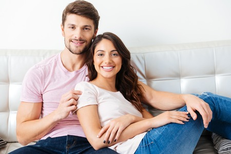 couple on couch: Happy smiling couple sitting on the couch over white background Stock Photo
