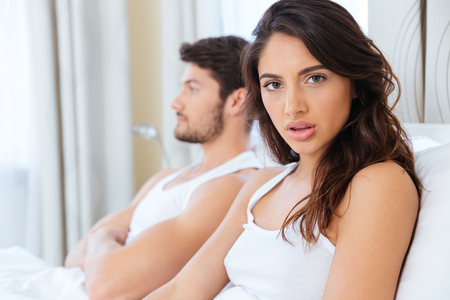 dysfunction: Upset woman sitting in the bed with man on the back at home