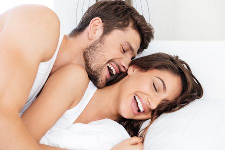 Feliz pareja joven y bella riendo juntos en la cama