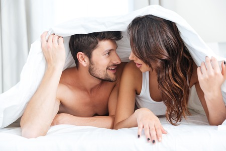 women talking: Happy couple lying in bed covered with blanket over head and talking at home over lights background